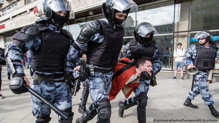 Police carry away a protester in Moscow