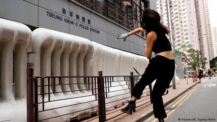 Hongkong Anti-Regierungsproteste - Demonstrantin wirft einen Stein auf die Polizeistation