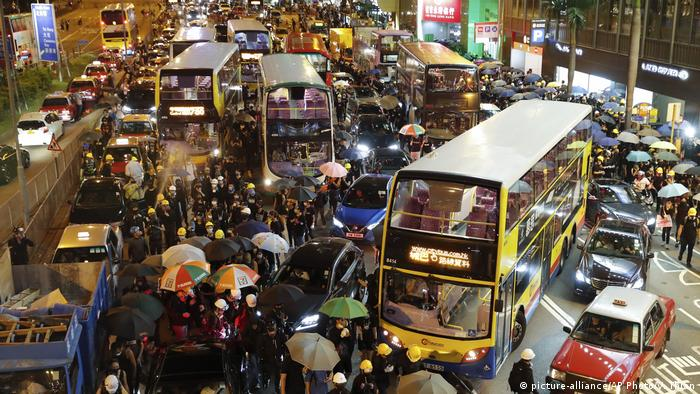 Buses, people and cars clog a street in Hong Kong
