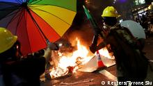 A demonstrator throws umbrellas into fire during an anti-extradition bill protest in Hong Kong, China, August 4, 2019. REUTERS/Tyrone Siu