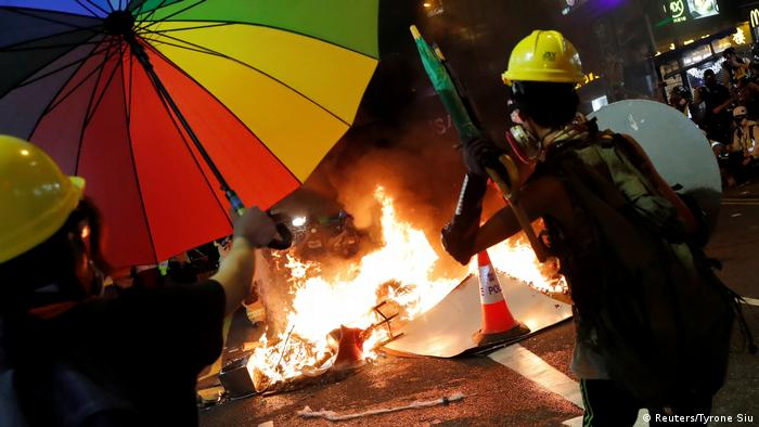 A demonstrator throws umbrellas into fire during an anti-extradition bill protest in Hong Kong - Generalstreik (Reuters/Tyrone Siu)