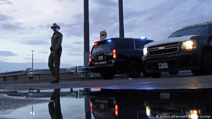 Law enforcement officials block a road at the scene of a mass shooting at an El Paso Walmart