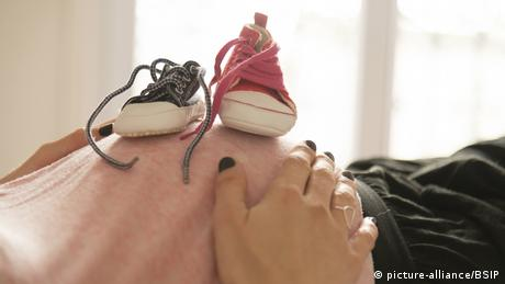 Blue and pink baby shoe on a pregnant belly (picture-alliance/BSIP)