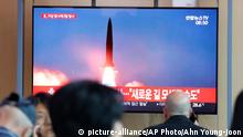 People watch a TV showing a file image of a North Korea's missile launch during a news program at the Seoul Railway Station in Seoul, South Korea, Tuesday, Aug. 6, 2019. North Korea on Tuesday continued to ramp up its weapons demonstrations by firing unidentified projectiles twice into the sea while lashing out at the United States and South Korea for continuing their joint military exercises that the North says could derail fragile nuclear diplomacy. The sign reads North Korea could seek a new road. (AP Photo/Ahn Young-joon)