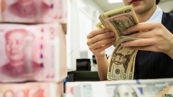 A Chinese bank employee counts 100-yuan notes and US dollar bills