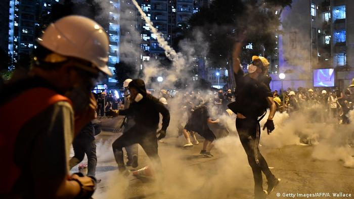 Protesters throw back tear gas fired by the police in Hong Kong on August 5