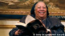 US author Toni Morrison (C) poses with her 1977 novel entitled Song of Solomon on September 21, 2012 during a reception sponsored by the US ambassador Charles H. Rivkin (R) at his residence in Paris, as part of the 10th America Festival. The America Festival is a cultural event held in France every two years which gathers well-known figures from the world of literature, music and cinema. AFP PHOTO / PATRICK KOVARIK (Photo credit should read PATRICK KOVARIK/AFP/GettyImages)