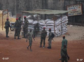 Guinean soldiers loyal to the ruling military junta stand outside an entrance to the main army base in Conakry, Guinea Monday, Dec. 7, 2009. Guinea's military strongman, hospitalized in Morocco with a gunshot wound, is conscious and speaking, the nation's foreign minister said Monday as he tried to tamp down speculation that Capt. Moussa Camara is badly hurt. (AP Photo/Rebecca Blackwell)