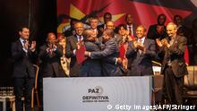 Mozambique's President Filipe Nyusi (C-L) and RENAMO (Mozambican National Resistence) leader Ossufo Momade (C-R) hug each other after signing a ceasefire agreement in Maputo, Mozambique, on August 6, 2019. - Mozambican President Filipe Nyusi and Renamo opposition leader Ossufo Momade signed a landmark agreement aimed at formally ending decades of military hostilities. (Photo by STRINGER / AFP) (Photo credit should read STRINGER/AFP/Getty Images)