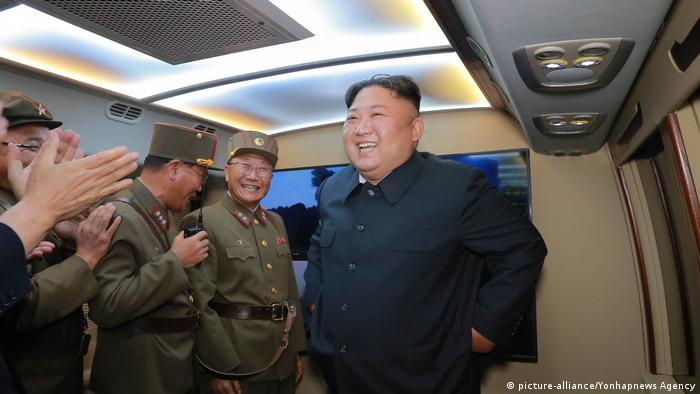 Kim Jong Un smiles as military men around him applaud