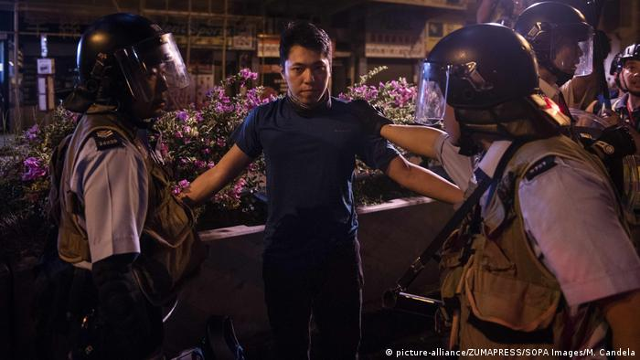 A protester is arrested by riot police officers in Hong Kong on August 7