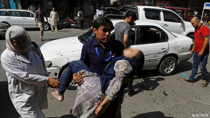 A man carries an injured woman to a hospital after a blast in Kabul