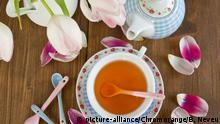 Frischer Tee in bunter Tasse und Tulpen in Vase