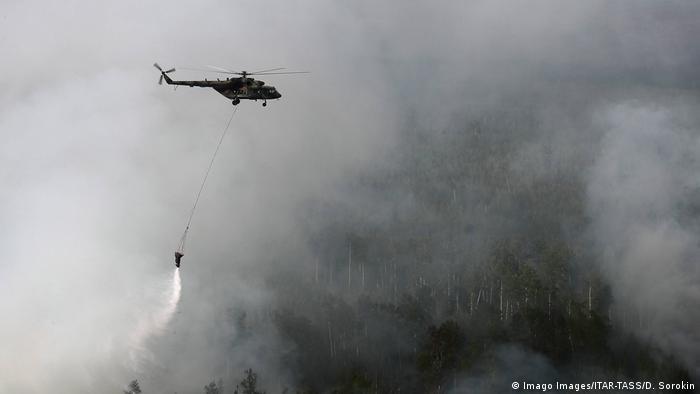 Вертолет тушит пожар, сбрасывая воду