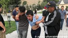People help a wounded man after shooting at former president of Kyrgyzstan Almazbek Atambayev's residence in the village of Koi-Tash, about 20 kilometers (12 miles) south of the capital, Bishkek, Kyrgyzstan, Wednesday, Aug. 7, 2019. Gunfire is being heard outside the residence of the former president of Kyrgyzstan as police move in to try to arrest him. (AKIpress via AP) |
