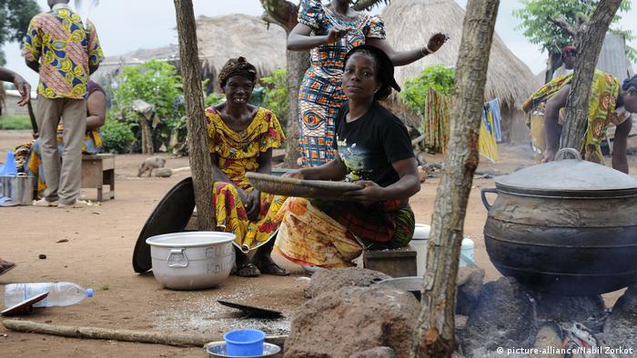 A woman cooks over a fire in Ivory Coast