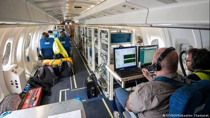 A group of researchers in a plane with computers and scientific equipment