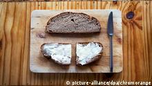 Vesperbrett mit Butterbrot auf antikem Holztisch