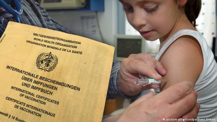 Child being vaccinated, Germany's yellow vaccination certificate