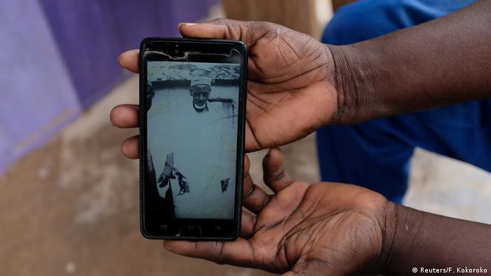 Abdul Sumud Shaibu, 50, showing a picture of his grandfather on his smartphone.