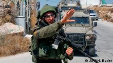 An Israeli soldier gestures during a house-to-house search operation in the West Bank village of Beit Fajjar near Bethlehem on August 8, 2019, following a stabbing attack. - An off-duty Israeli soldier was found dead with stab wounds near a Jewish settlement in the occupied West Bank today in what Prime Minister Benjamin Netanyahu called a terrorist attack, sparking a manhunt. Details were still emerging of the killing, but it risked raising Israeli-Palestinian tensions weeks ahead of September 17 Israeli polls. (Photo by HAZEM BADER / AFP)