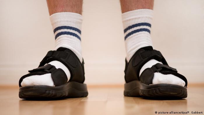Männerfüße in weißen Socken und Sandalen