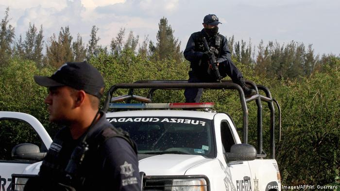 A policeman holding a gun stands on a police truck