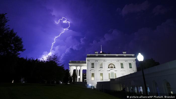 A bolt of lightening illuminates the sky behind the white house