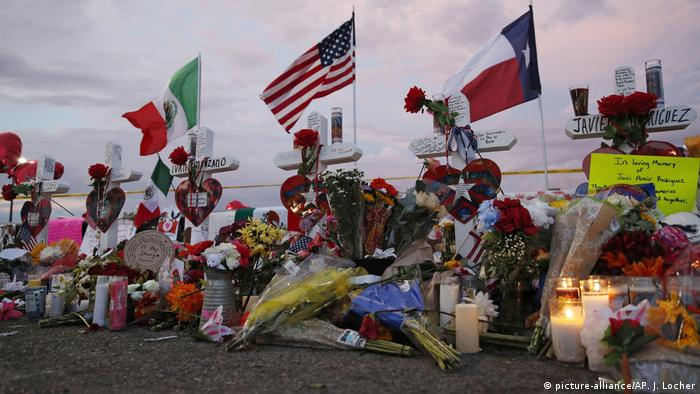 A makeshift memorial with flowers and candles at the site of the El Paso shooting
