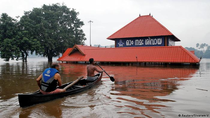 Rescuers row a boat to a submerged temple