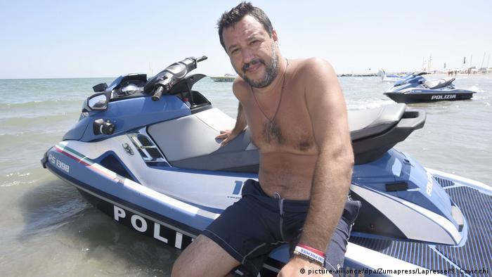 Premiê italiano, Matteo Saivini, sentado em barco da polícia à beira-mar