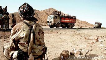 Eritreischer Soldat beobachtet Soldaten auf Lastwagen auf dem Weg nach Akurdet
