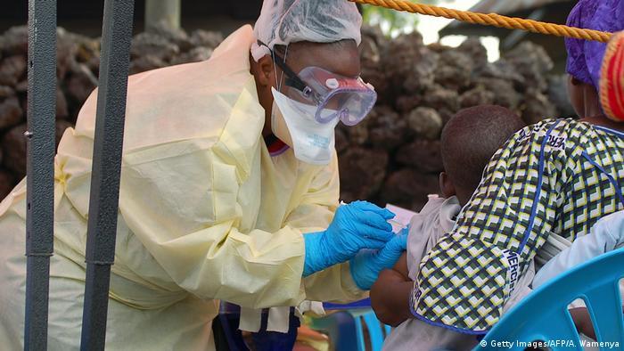 Vacunando a un niño contra el ébola en África.