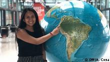 Die Deutschlernerin Aitana aus Ecuador steht an einem Globus und zeigt mit dem Finger auf ihr Land