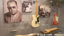 Leo Fender und seine frühen Modelle im Fender Guitar Factory Museum. Quelle: https://de.wikipedia.org/wiki/Leo_Fender#/media/Datei:FGF_museum_01._Leo_and_early_models.jpg