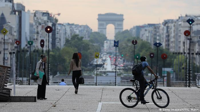 People walk through an art installation entitled Le Bassin by Greek sculptor Panagiotis Vassilakis, also known as Takis, in the La Defense business district in suburban Paris, with the Arc de Triomphe in the background