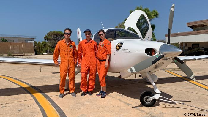 Three Sea-Watch Moonbird crew members in orange jumpsuits