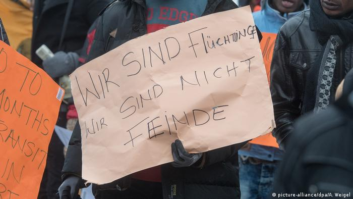 An asylum-seeker holds up a sign at a protest in Deggendorf that reads: We are refugees. We are not enemies.