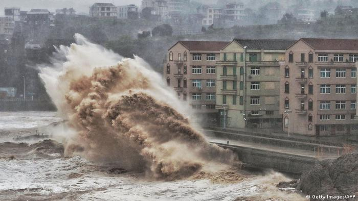 Waves hit a sea wall in front of buildings in Taizhou, China