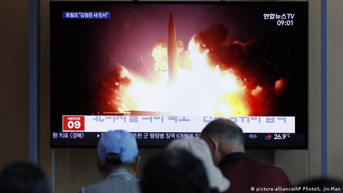 People watch a TV report in South Korea showing the launch of a missile from North Korea