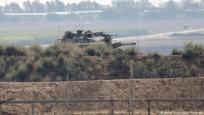 An Israeli tank sits near the separation wall between Israel and Gaza