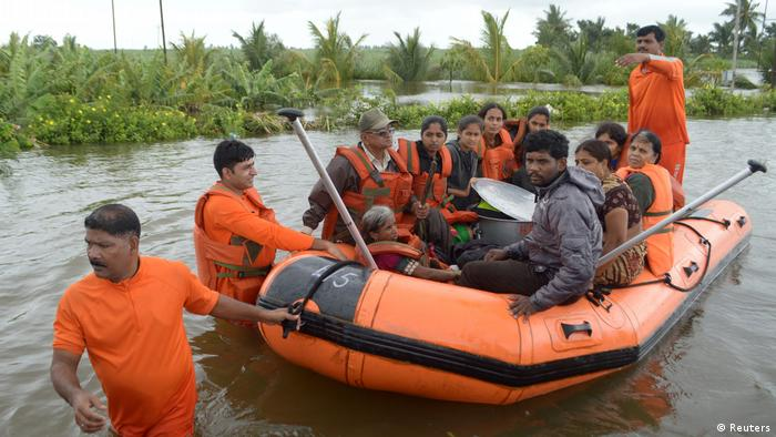 Rescuers drop an inflatable boat that takes people affected by floods to a safe place in Maharashtra (Reuters)