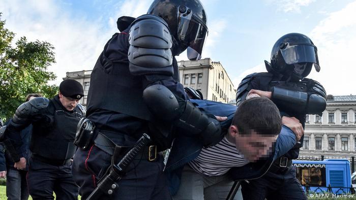 Police holding a man (AFP/V. Maximov)