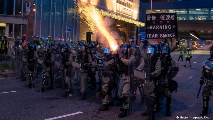 Ein Polizist schießt am Sonntag Tränengas in Richtung der Demonstranten