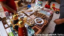 August 10, 2019*** Libyans eat desserts after breaking their fast on the evening prior to the start of the Muslim religious festival of Eid al-Adha in the Libyan capital Tripoli on August 10, 2019. - Known as the big festival, Eid Al-Adha is celebrated each year by Muslims sacrificing various animals according to religious traditions, including cows, camels, goats and sheep. (Photo by Mahmud TURKIA / AFP) (Photo credit should read MAHMUD TURKIA/AFP/Getty Images)