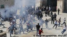 Palestinians run for cover from sound grenades at the al-Aqsa Mosque compound in the Old City of Jerusalem on August 11, 2019, as clashes broke out with Israeli forces during the overlapping Jewish and Muslim holidays of Eid al-Adha and the Tisha B'av holiday inside the historic compound which is considered the third-holiest site in Islam and the most sacred for Jews, who revere it as the location of the two biblical-era temples. - The compound, which includes the Al-Aqsa mosque and the Dome of the Rock, is one of the most sensitive sites in the Israeli-Palestinian conflict. (Photo by Ahmad GHARABLI / AFP) (Photo credit should read AHMAD GHARABLI/AFP/Getty Images)
