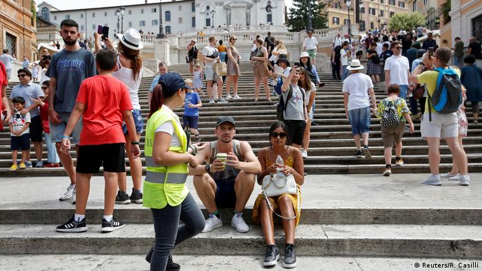 A municipal policewoman asks tourists to stop sitting on Rome's Spanish Steps