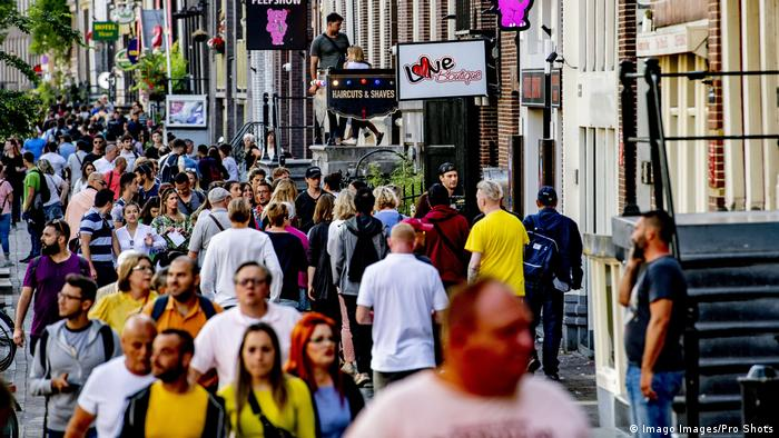 Pessoas caminhando numa rua de Amsterdã