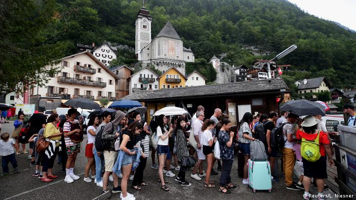Tourists queue to board a boat for a trip on Hallstaettersee lake in Hallstatt, Austria