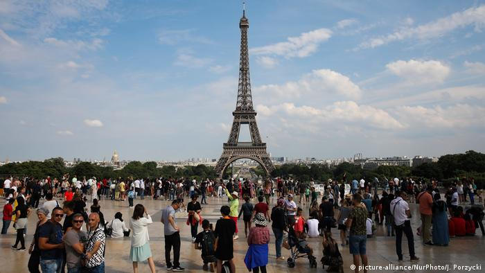 Tourists gather at the Place du Trocadero overlooking the Eiffel Tower in Paris, France